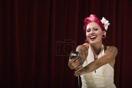 Tattooed Hispanic woman laughing on stage