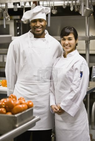 Multi-ethnic male and female chefs in kitchen