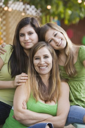 Hispanic mother and daughters hugging