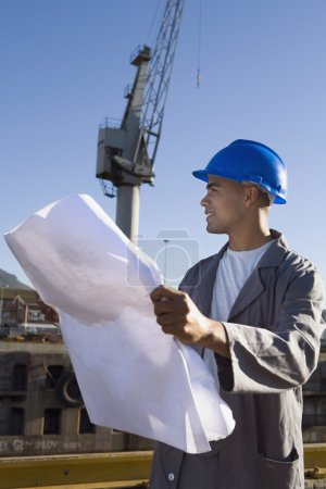 African American construction worker holding blueprints