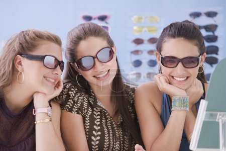 Multi-ethnic teenaged girls trying on sunglasses