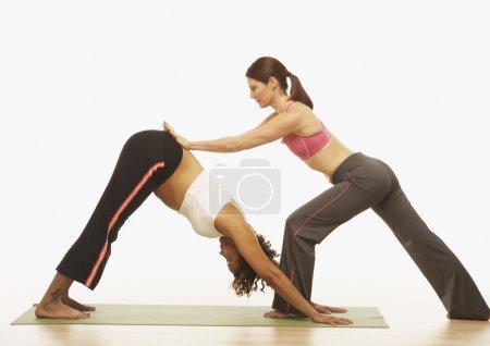 Yoga trainer assisting pregnant woman