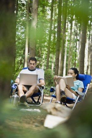 Hispanic couple relaxing in woods