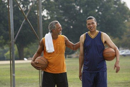 men holding basketballs