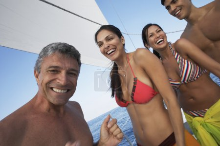 Multi-ethnic couples laughing on sailboat