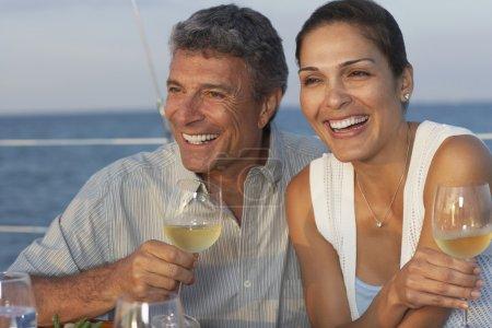 Multi-ethnic couple drinking wine on boat