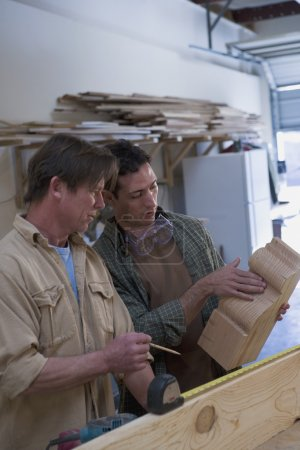 Multi-ethnic men working in wood shop