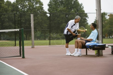men talking on tennis court