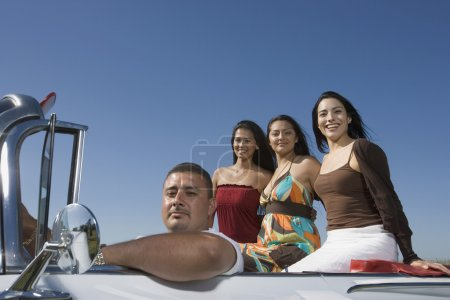 Hispanic man with three women in convertible