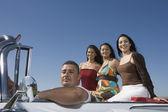 Hispanic man with three women in convertible