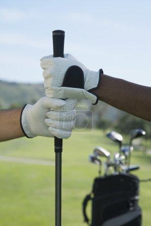 Multi-ethnic men holding golf club