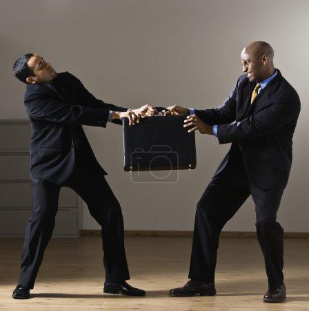 Multi-ethnic businessmen fighting over briefcase