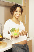 Pregnant Mixed Race woman holding bowl of vegetables