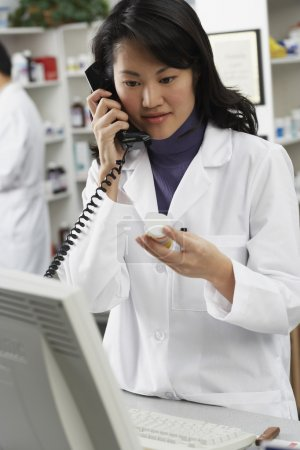 Asian female pharmacist talking on telephone