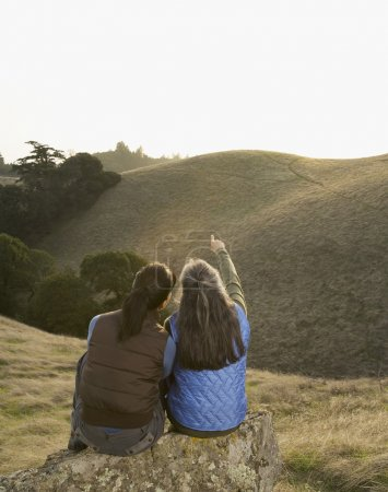 Two women pointing at hill in countryside