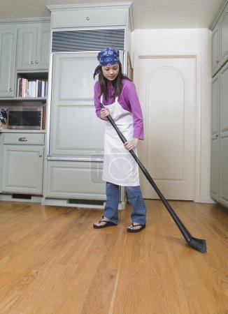 Woman sweeping kitchen floor