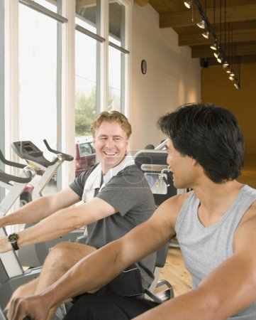 Two men using exercise bikes in health club