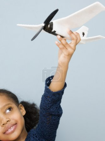 Mixed race girl playing with toy airplane