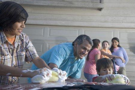 Hispanic father and sons washing car