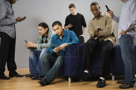 Group of multi-ethnic men text messaging on cell phones
