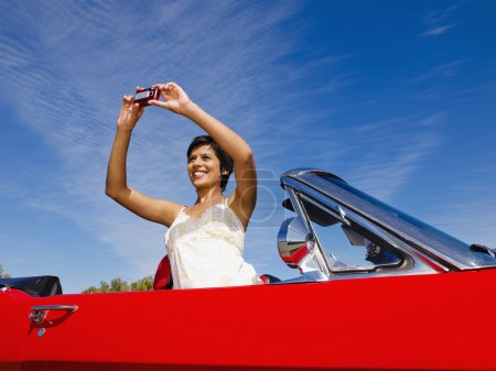 Mixed race woman taking photograph from red convertible