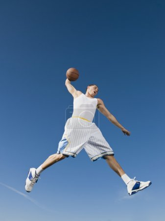 African man playing basketball in mid-air