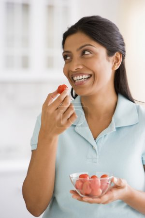 Indian woman eating tomato