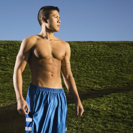 Bare chested Asian man standing in park