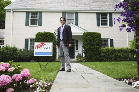 Male real estate agent and Sold sign in front of house
