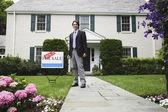 agent immobilier mâle et vendu signe en face de la maison
