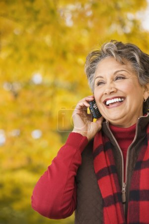 African woman using cell phone outdoors in autumn