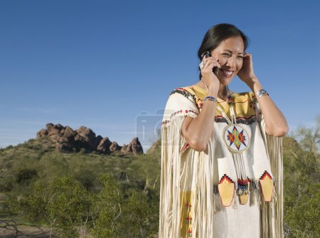Native American woman in traditional clothing talking on cell phone outdoors