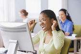 African businesswoman cheering at desk