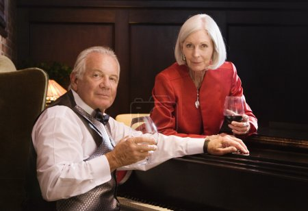 Well dressed senior couple drinking wine next to piano