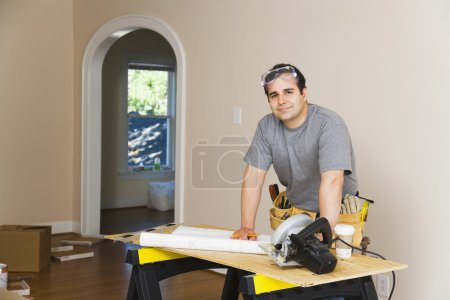 Hispanic man remodeling interior of home