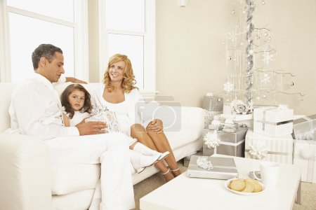Hispanic family sitting on sofa at Christmas
