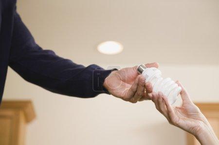 Hispanic man handing woman compact fluorescent light bulb