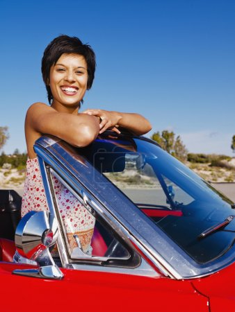 Mixed race woman in red convertible