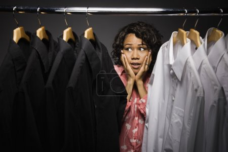 Uncertain mixed race woman looking at shirts in closet