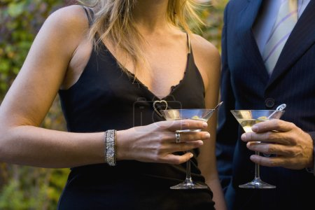 Close up of couple in fancy clothing holding martinis