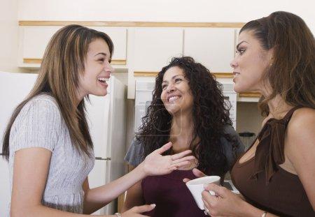 Multi-generational women talking in kitchen