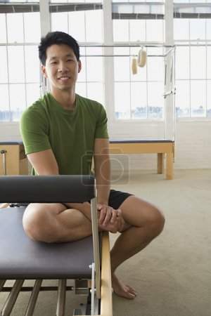 Asian man sitting in exercise studio