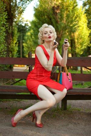 Photo pour Pin up femme appliquant son maquillage assis sur un banc dans le parc - image libre de droit