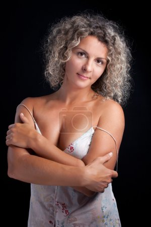 Curly mature woman wearing lingerie posing black background