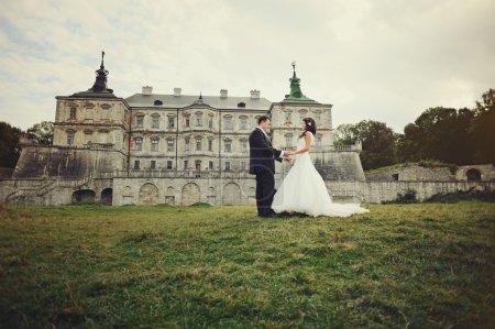 Photo pour Mariage, marié et mariée tenant la main à côté du vieux château dans l'ouest de l'Ukraine - image libre de droit