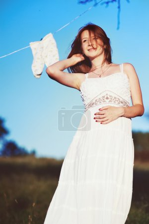 Beautiful young pregnant woman in garden.