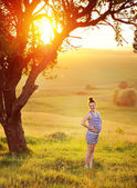 Krásná mladá těhotná žena v zahradě