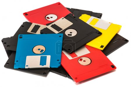 Old obsolete colored floppy disks on a white background