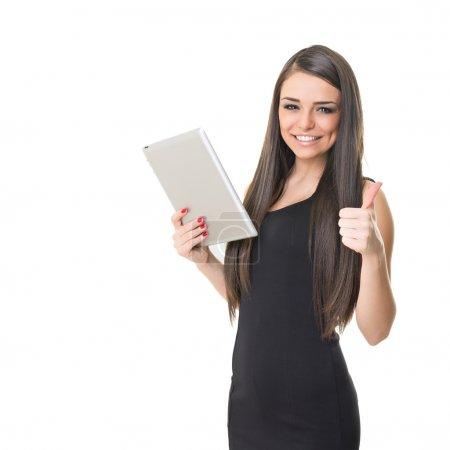 Photo pour Heureuse caucasienne élégante prospère à l'aide d'une tablette numérique porter petite robe noire et montrant le pouce en haut isolé sur fond blanc. - image libre de droit