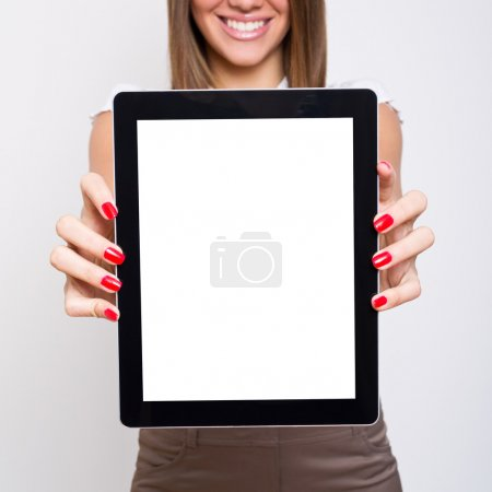 Photo for Beautiful young Caucasian woman showing digital tablet blank screen. The tablet is in focus and the model is blurred in the background .square photo format. Isolated tablet screen for your design, text, photo etc. - Royalty Free Image